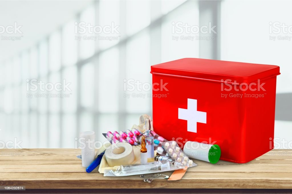 First aid kit with medical supplies on background
