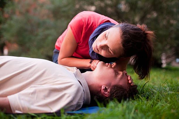 first aid - look, listen and feel for breathing. - first aid stock photos and pictures