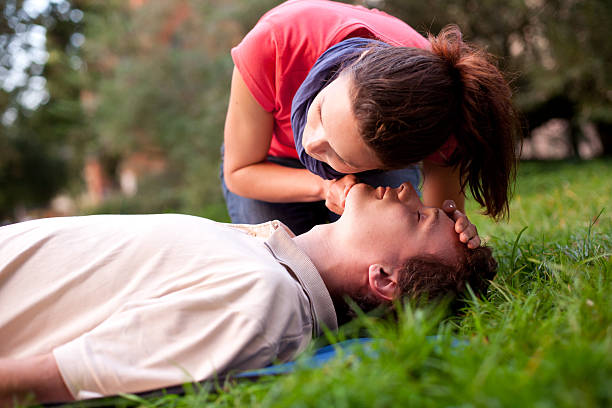 First aid - Look, listen and feel for breathing. First aid - Look, listen and feel for breathing. Woman is performing first and on a man laying in the grass. She is pulling his head back, listening to his breath and looking at his chest to check if he is breathing. The man is laying unconscious.  woman taking pulse stock pictures, royalty-free photos & images
