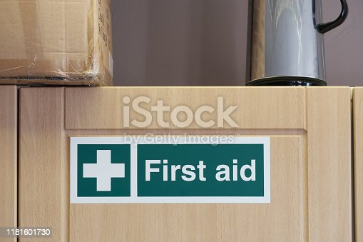 istock First Aid sign located on an office kitchen cupboard, containing a first aid kit needed by UK law. 1181601730