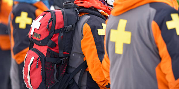 First aid ski patrol with backpacks stock photo