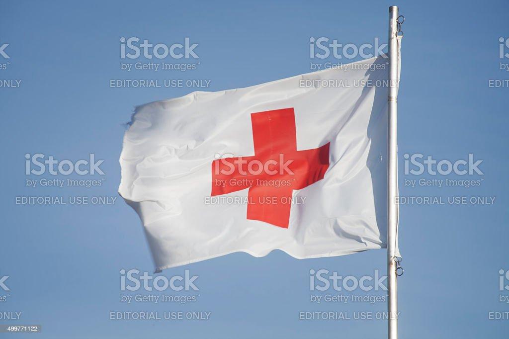 Primeiros socorros/Medic Cruz Vermelha bandeira e céu azul. - foto de acervo