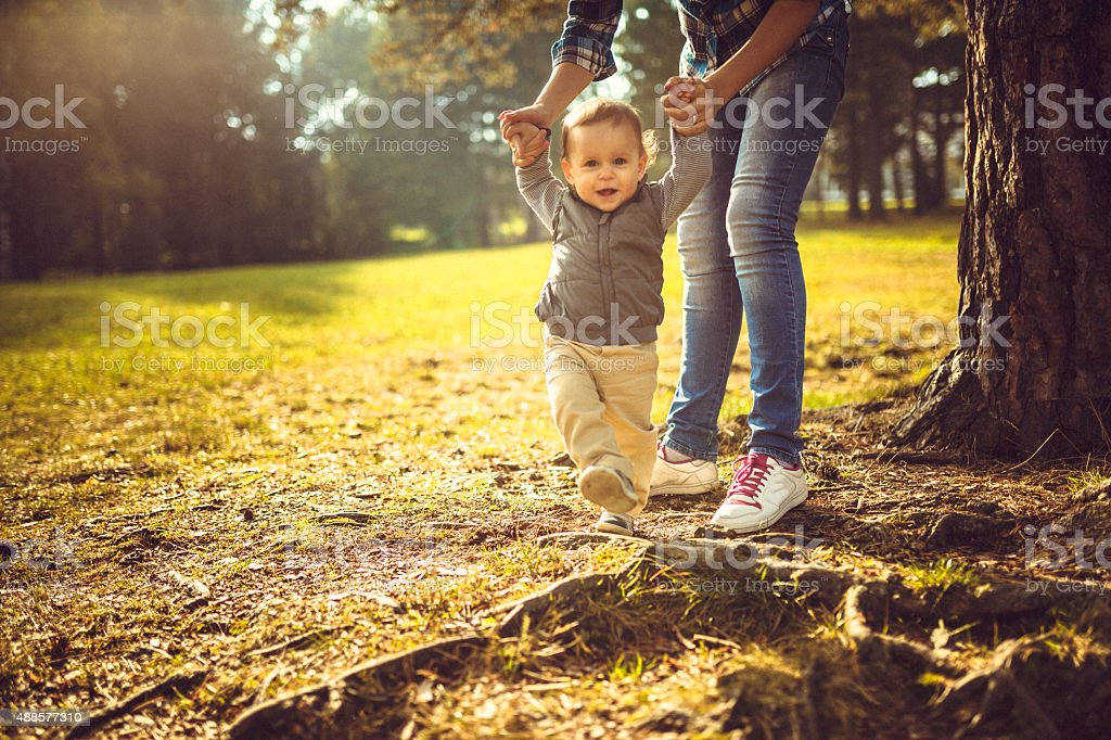 First baby steps in the park stock photo