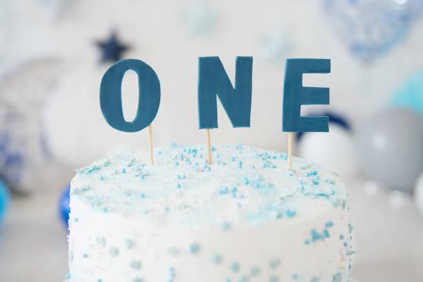 ersten geburtstagskuchen. kuchen zu zerschlagen. ein jahr.  blaue briefe, sagt man. - nummer 1 kuchen stock-fotos und bilder