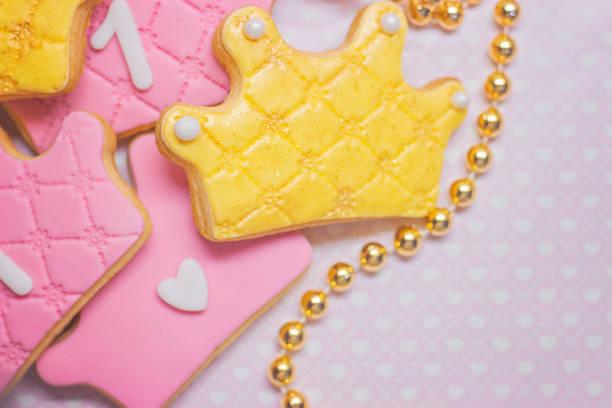 erster geburtstag krone geformt königlicher zuckerglasur cookies auf rosa hintergrund - prinzessinnen torte stock-fotos und bilder