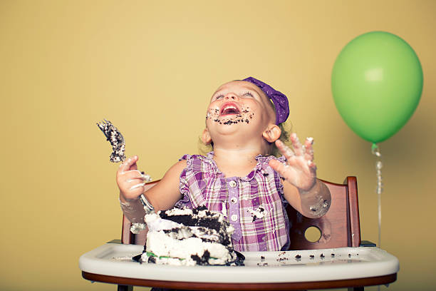 First Birthday Let them eat cake and enjoy it. A girl celebrates her first birthday. first birthday stock pictures, royalty-free photos & images