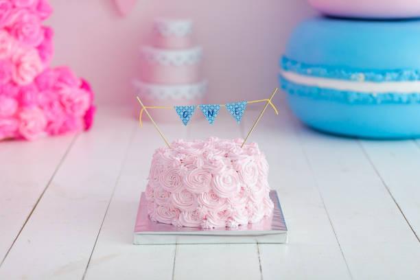 ersten geburtstag den kuchen zu zerschlagen. ein rosa kuchen steht auf einem weißen hintergrund aus holz. ersten geburtstag. - windel partys stock-fotos und bilder