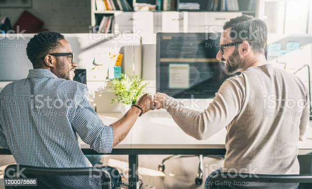 First Bump Between Colleagues At Work Everyday Work In The Office - Fotografias de stock e mais imagens de Amizade
