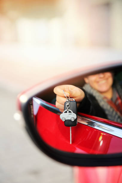 First car - young woman with keys stock photo