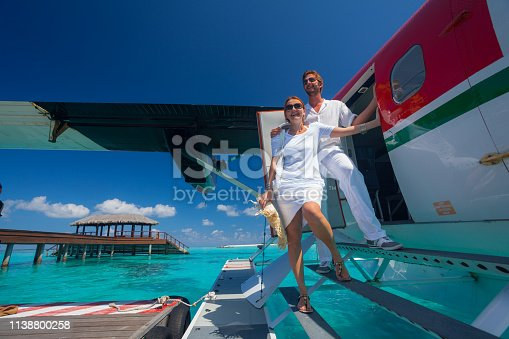 luxury travel couple arriving on tropical island with seaplane