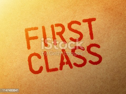 Close-up of word First Class stamped on brown paper.