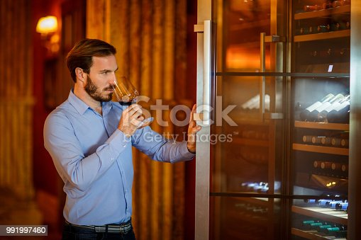 Male person is having a glass of wine during luxury travel to winery.
