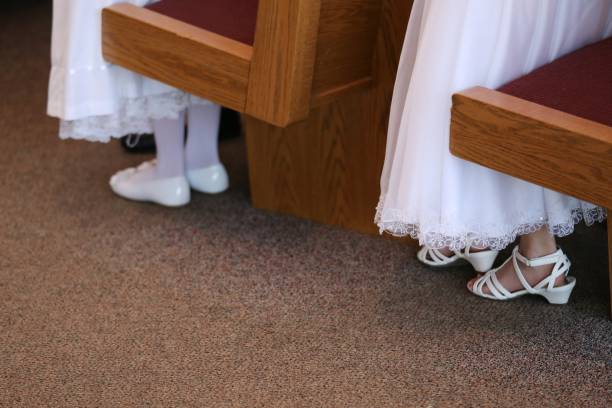 First Communion Girls Wearing White Dresses and Shoes, Church Pew stock photo