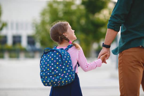 erster Schultag. Vater führt kleine Kind Schulmädchen in der ersten Klasse – Foto