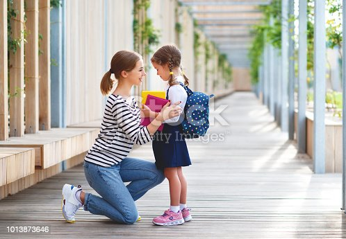 istock first day at school. mother leads  little child school girl in first grade 1013873646