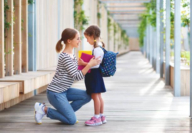 erster Schultag. Mutter führt kleine Kind Schulmädchen in der ersten Klasse – Foto