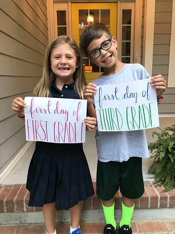 A brother and sister stand in front of their house on the fist day of first and third grades.