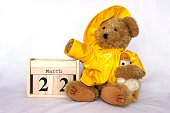 istock First day of spring wooden calendar with teddy bear wearing yellow rain coat 1331989445