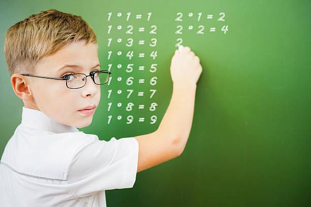 Primer grado niño en edad escolar en pizarra escribió multiplicación mesa - foto de stock