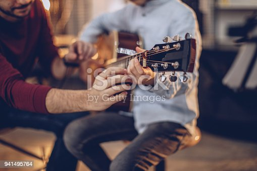 Two people, man guitar teacher working with little boy on guitar lessons.