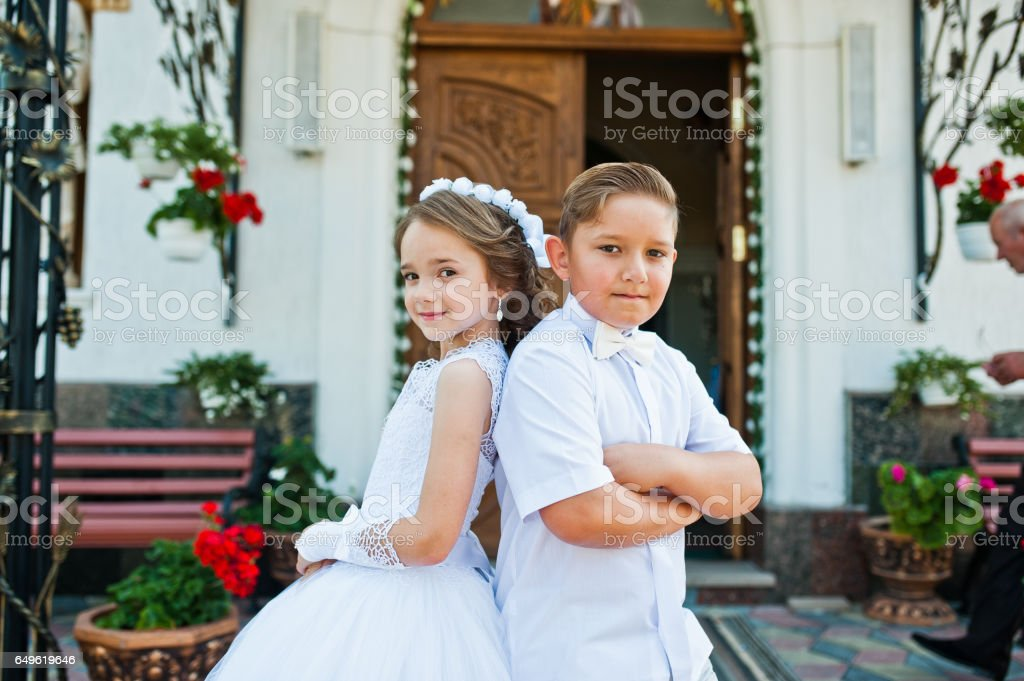 First holy communion, brother and sister stay at white dress background church stock photo
