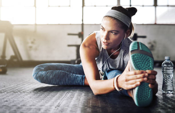 First I stretch then I do my intense exercises Shot of an attractive young woman stretching at the gym touching toes stock pictures, royalty-free photos & images