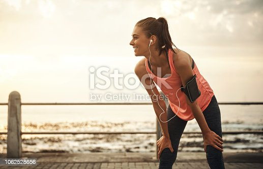 Shot of a young woman taking a break from running on a promenade at sunset