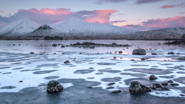 Primeira luz em um Lochan congelado na h-achlaise - foto de acervo