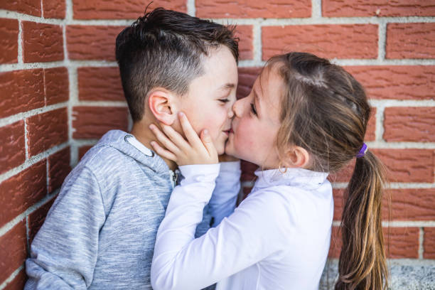 first love and kiss two happy cute kids meeting - little girls little boys kissing love stock photos and pictures