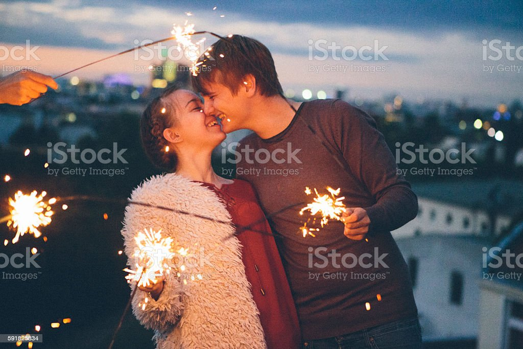 first love: young adult couple kiss in front of sparklers stock photo