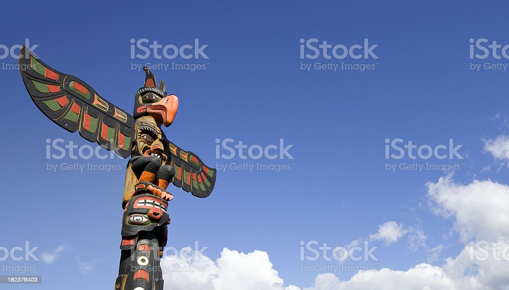 First Nations Totem Pole against Blue Sky stock photo