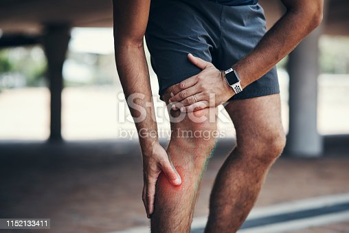 Closeup shot of an unrecognizable man holding his leg in pain while exercising outdoors