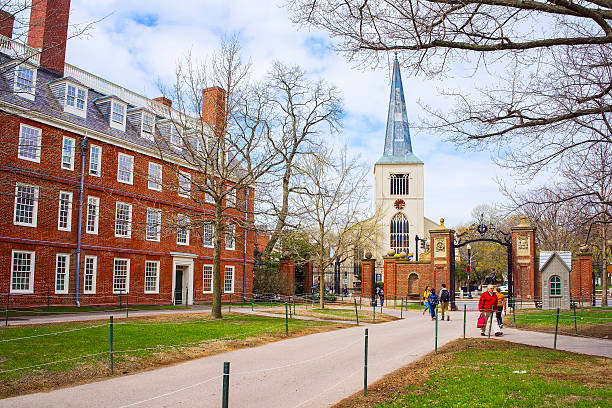 First Parish Church and tourists in Harvard Yard Cambridge, United States - April 29, 2015: First Parish Church in Harvard Square and tourists in Harvard Yard in the campus of Harvard University, Massachusetts, MA, USA. The church is built 400 years ago. harvard university stock pictures, royalty-free photos & images