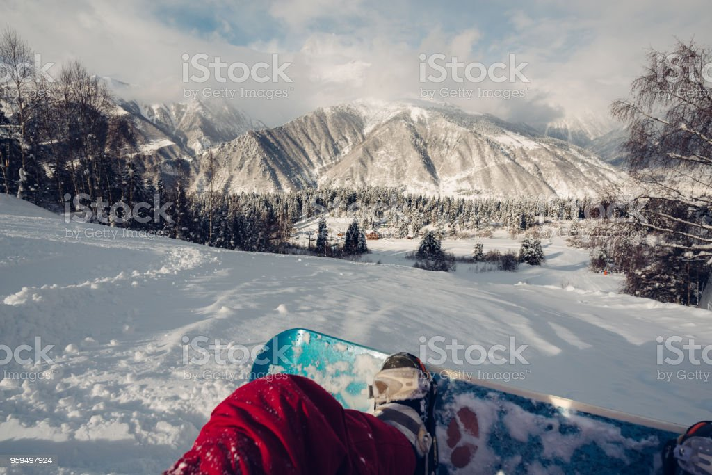 first person is sitting on the snowing hill stock photo