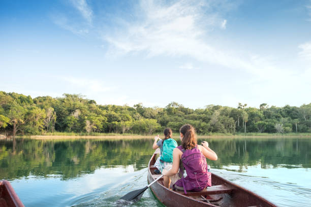 First Person Perspective of Sisters with Backpacks Canoeing in Lake stock photo
