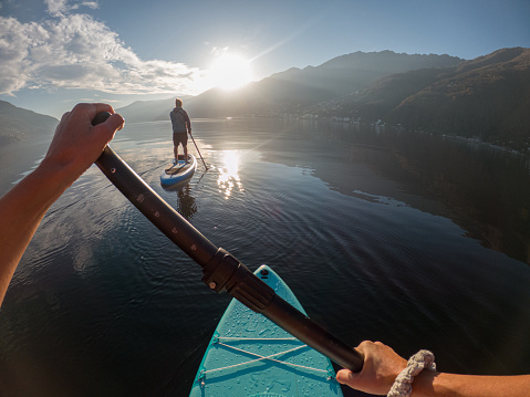 Man paddling with her, mountains in distance