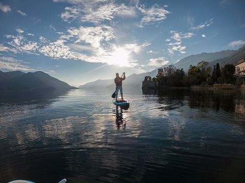 First person point of view of a woman paddling on a stand up paddle board on a lake at sunset