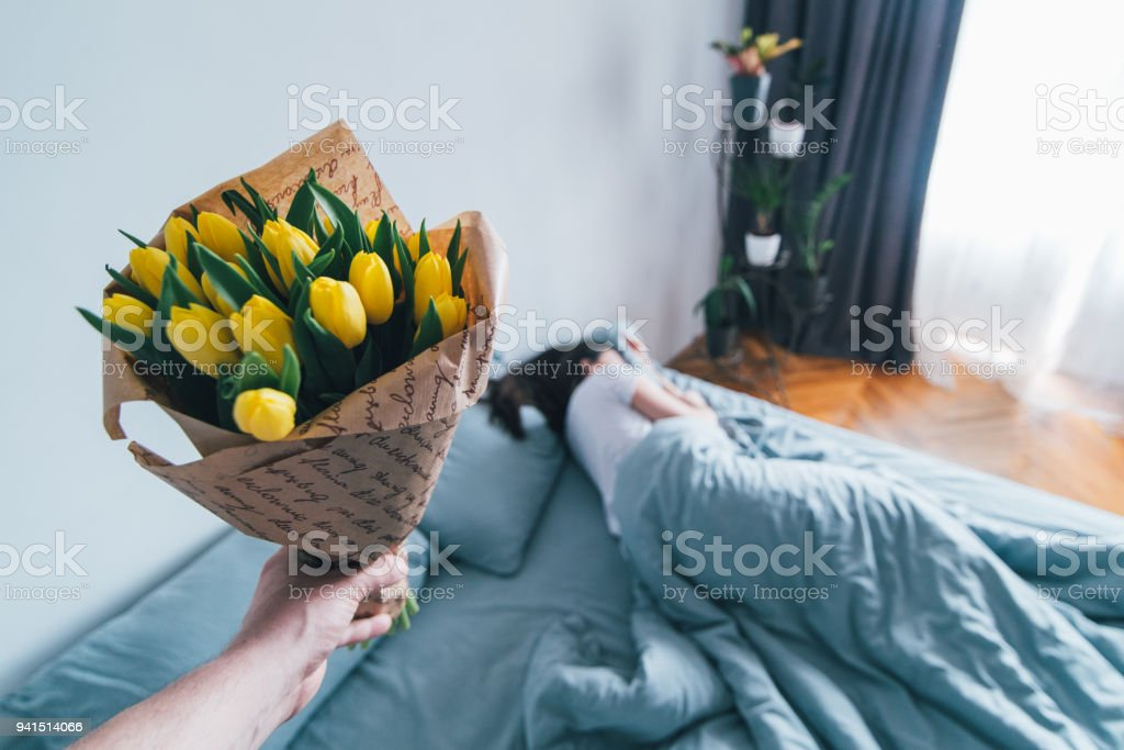 first person view. man bring flowers to bed for sleeping girlfriend. romantic surprise concept stock photo