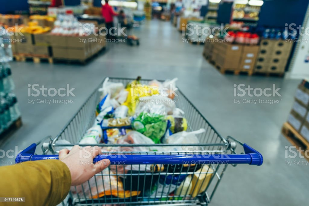 first person view. man with trolley in grocery store. shopping concept stock photo