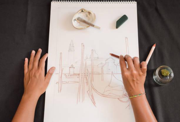 first-person-ansicht einer frau, die mit einem bleistift zeichnet, während sie einen marihuana-joint raucht. schwarzer tisch mit skizze, lässiger muschelaschenbecher und cannabis. - bemalte muscheln stock-fotos und bilder
