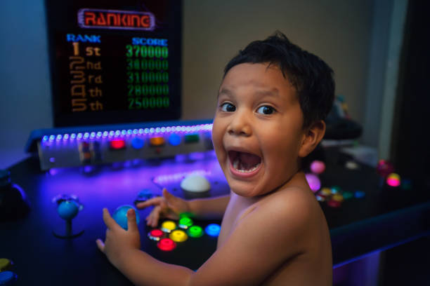First place ranking or high score by a young gamer with an enthusiastic expression while gaming on a home arcade. stock photo
