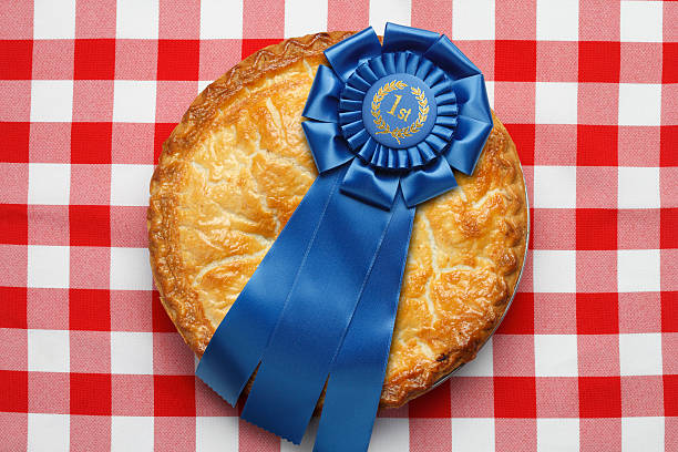 first place ribbon on pie sitting on red checkerboard tablecloth - award ribbon stock photos and pictures