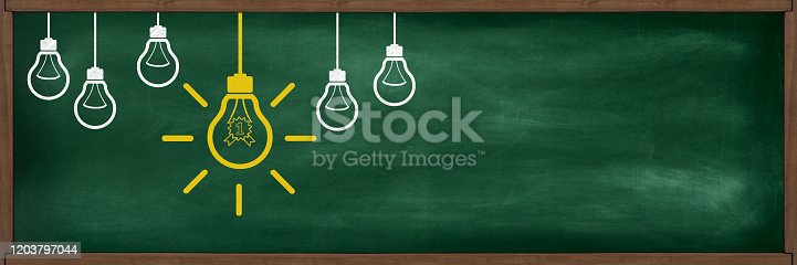 Business and achievement concept; 0ne glowing yellow lightbulb with first award icon between not glowing regular white lightbulbs on 3D greenboard with wooden frame. Panoramic composition with large copy space.