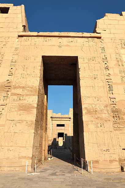 """First Pylon, Medinet Habu, Theban Necropolis, Luxor, Egypt """"The first pylon of Medinet Habu, the mortuary temple of the 12th century BC pharaoh Ramesses III (also Ramses, Rameses and Usermaatre-meryamun).  Located on the West Bank in the southern part of the Theban necropolis, Medinet Habu is one of the finest temples in Egypt."""" Tomb Of Ramses III stock pictures, royalty-free photos & images"""