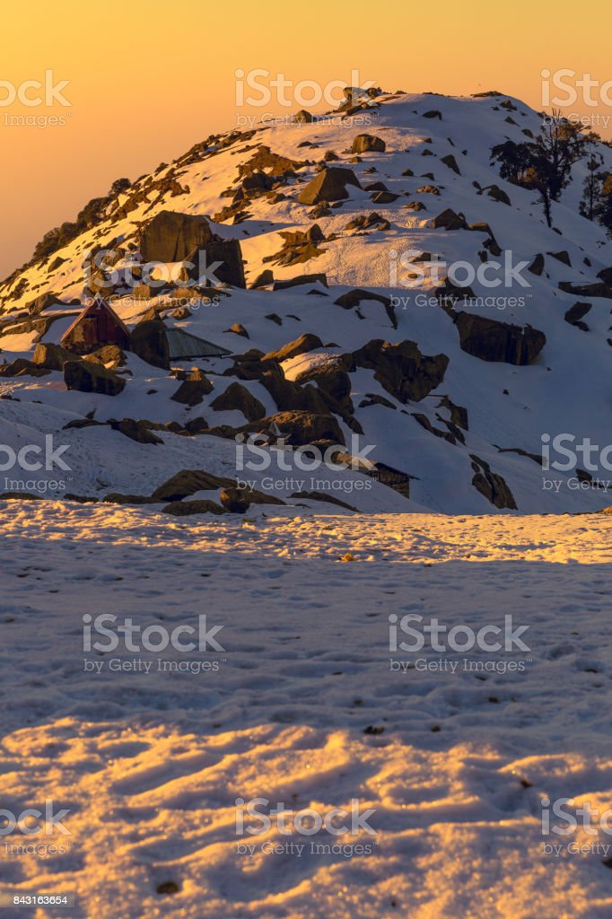 First rays of sun falling on a snow mountain called Triund in Mcleodganj,Dharamshala, Himachal pradesh, India at golden hour. stock photo