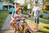 Shot of happy young brothers riding a bicycle together in their backyard
