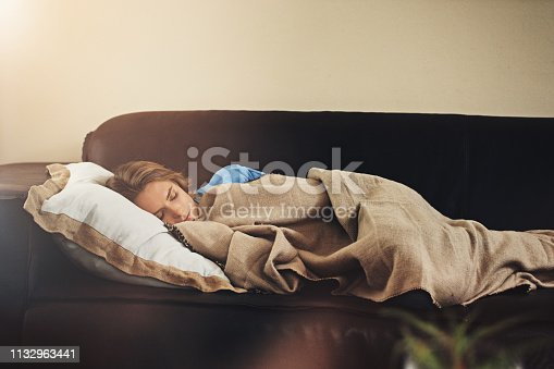 Shot of a young woman sleeping peacefully on the sofa at home