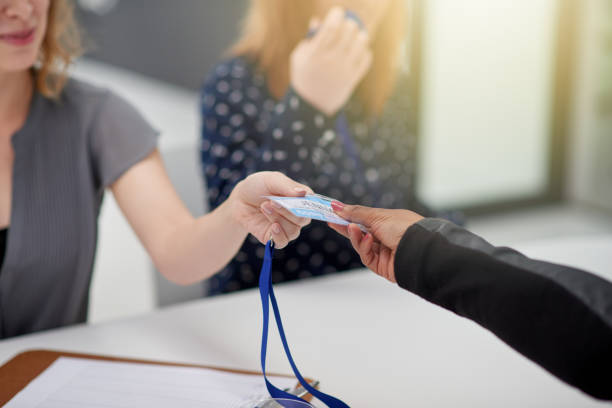 First sign in then you can attend the seminar Closeup of an unrecognizable businesswoman handing over a access card to a newly signed up client to attend a seminar during the day security pass stock pictures, royalty-free photos & images