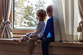 A boy and a girl sitting on a window in the morning and watching first snow.