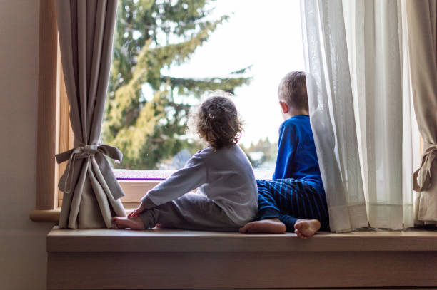First snow A boy and a girl sitting on a window in the morning and watching first snow. boy looking out window stock pictures, royalty-free photos & images